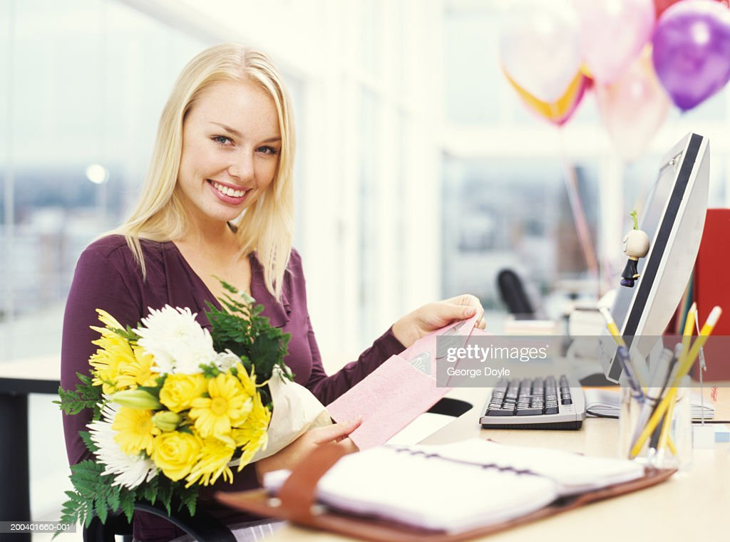 Young woman opening greeting card and holding bouquet, portrait