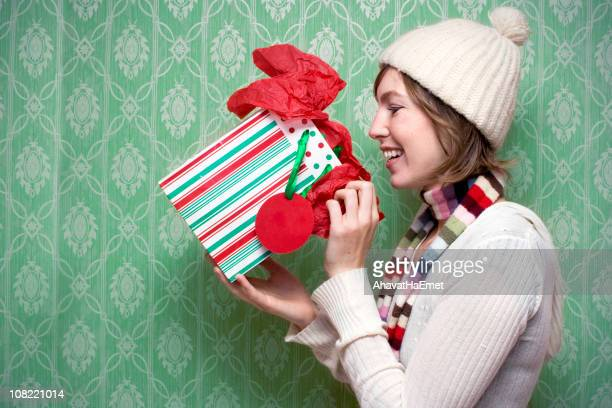 Young woman opening her present at holidays