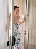 Young Woman Opening Sliding Glass Door