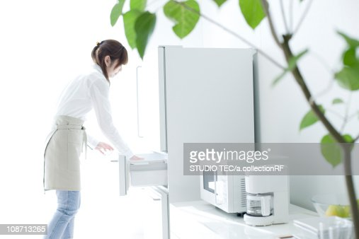 Young woman opening the refrigerator