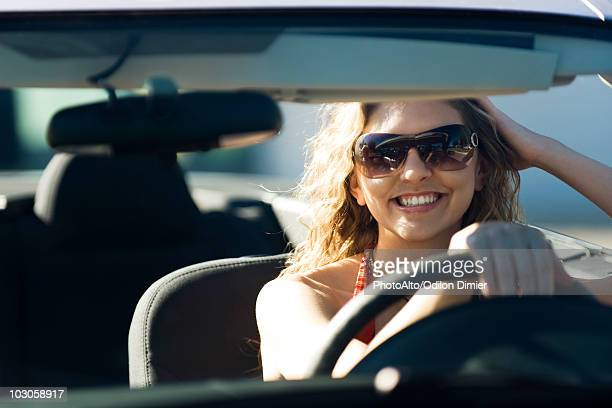 Young woman out for drive on sunny day