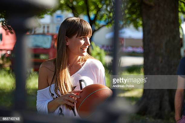 Young woman outdoors, holding basketball, smiling