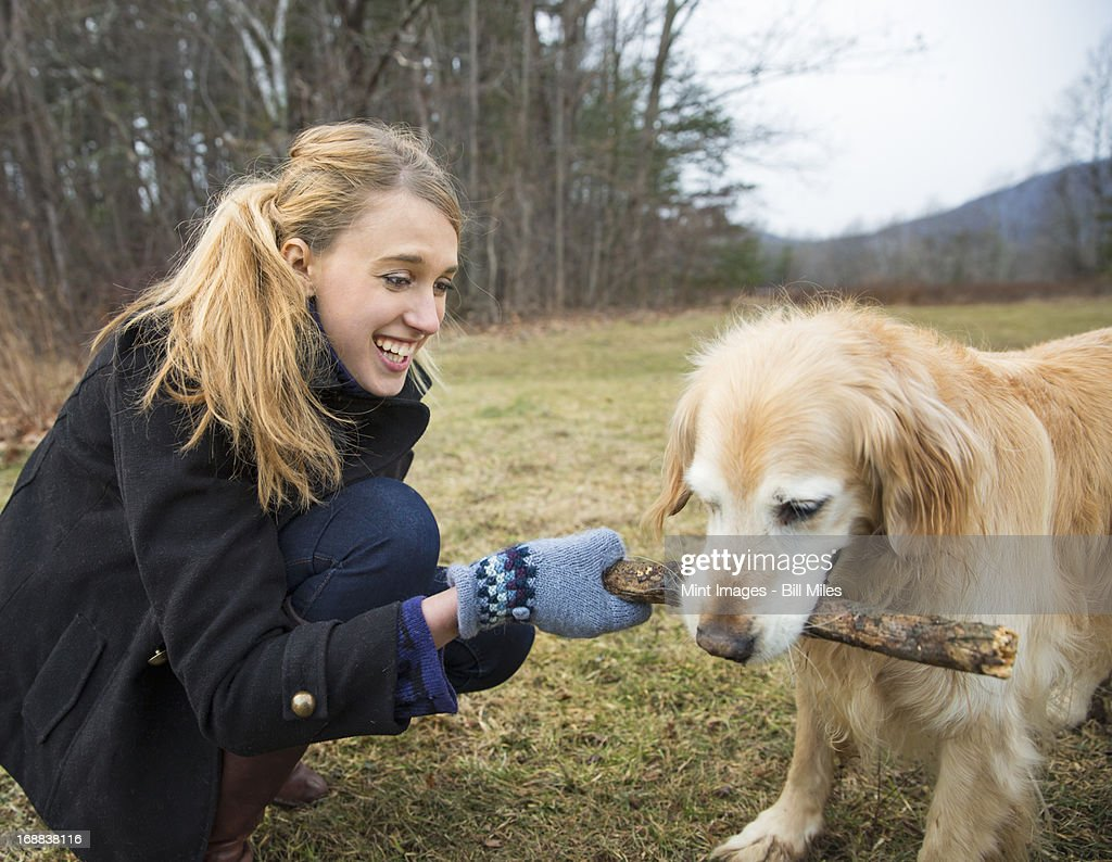 A young woman outdoors in the winter, on a walk with a golden retriever dog.  : Stock Photo