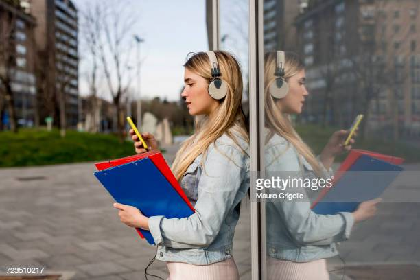 Young woman, outdoors, leaning against window, wearing headphones, holding smartphone and document files