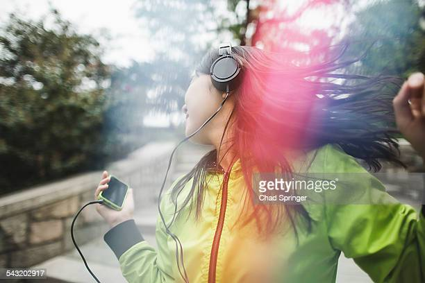 Young woman, outdoors, listening to music and dancing