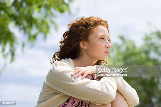 Young woman outdoors, looking away in thought