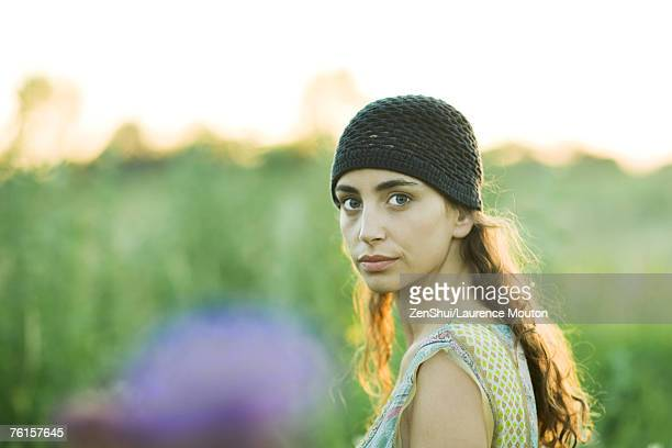 Young woman outdoors, looking over shoulder at camera