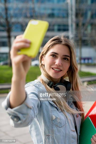 Young woman, outdoors, taking selfie with smartphone