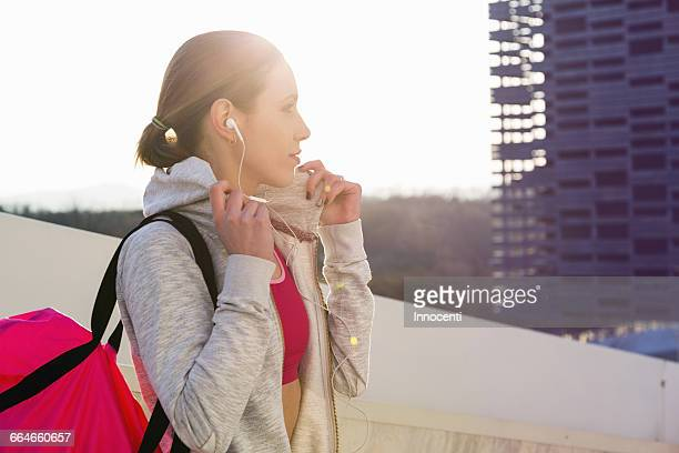 Young woman outdoors, wearing sports clothing and earphones, carrying sports bag