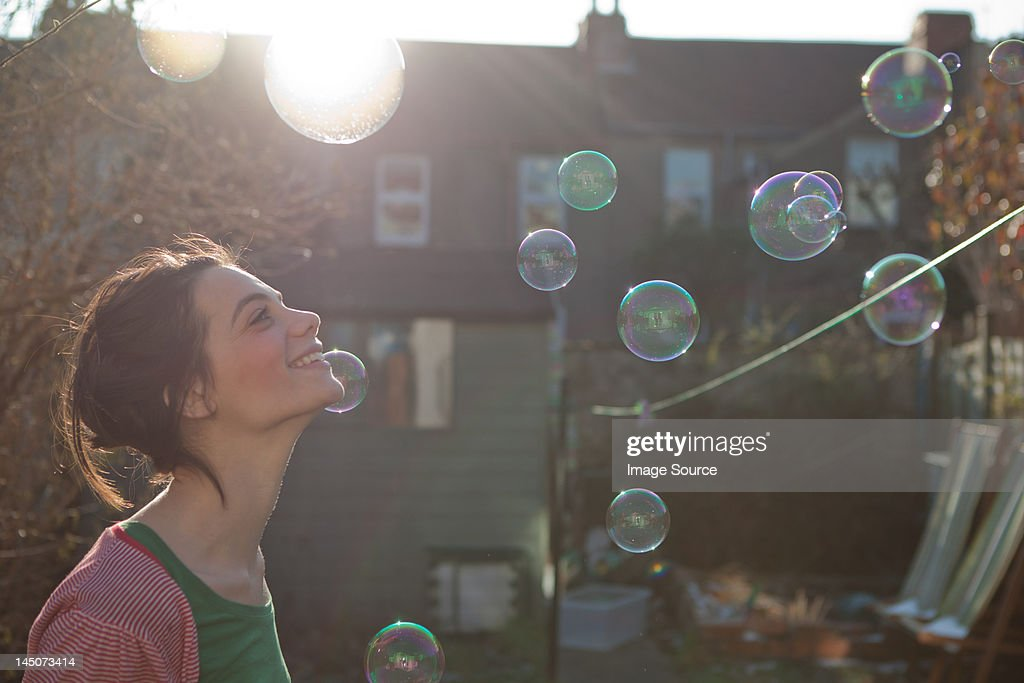 Young woman outdoors with bubbles floating in air : Stock Photo