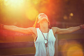 Young woman outstretched arms enjoys the freedom and fresh air