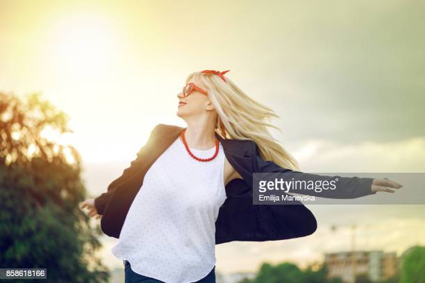 Young woman outstretched arms enjoys the freedom