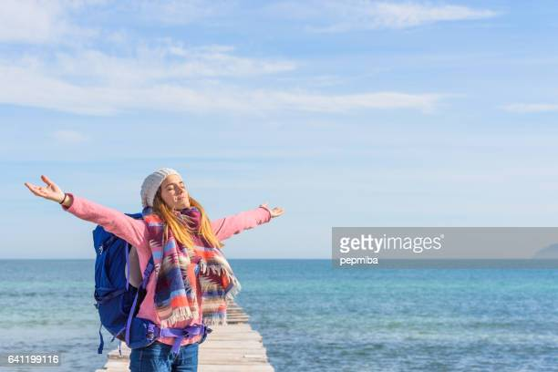 Young woman over pier with open arms