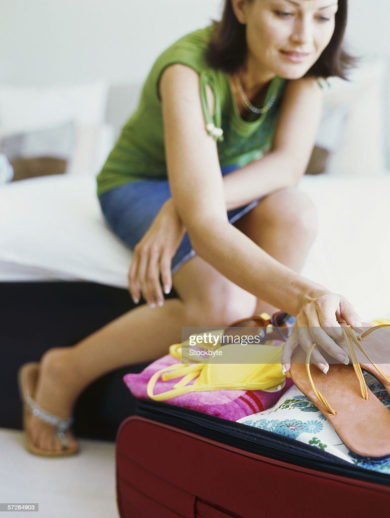 Young woman packing her luggage