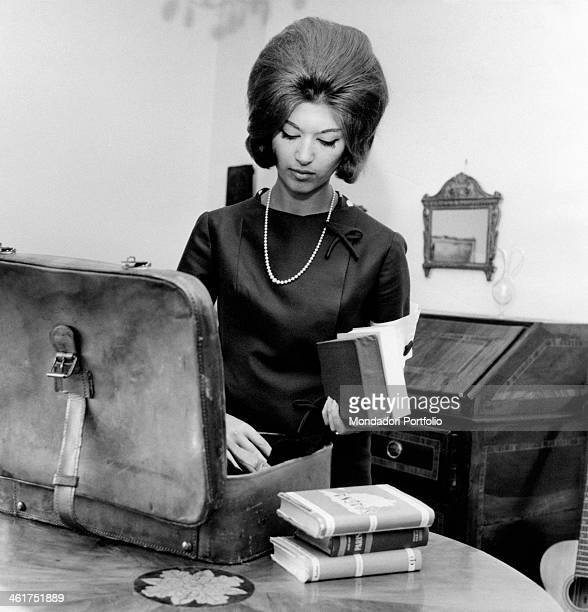 A young woman packing some books in a suitcase 1960s