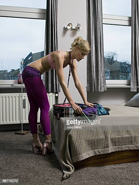 young woman packing suitcase in apartement