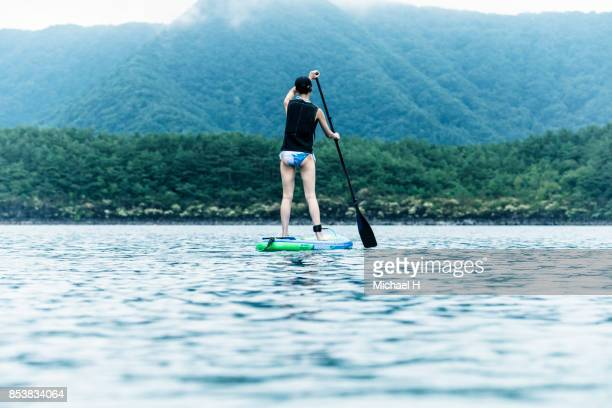 Young woman paddle boarding