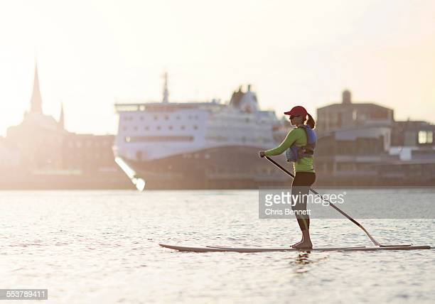 A young woman paddleboards across the harbor in Portland, Maine.