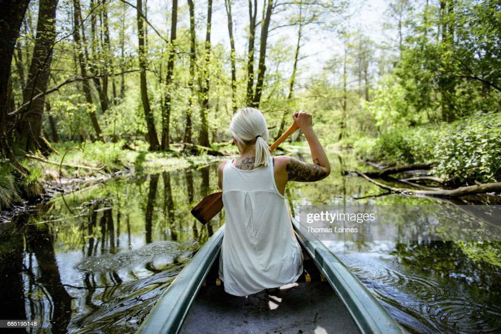 A young woman paddles a canoe on the creek 'Loecknitz' in Brandenburg state on May 19, 2017 near Erkner, Germany. Brandenburg, with its multitude of waterways and lakes that are rich in plant and wildlife, is a popular destination for canoeing and other water sports enthusiasts.