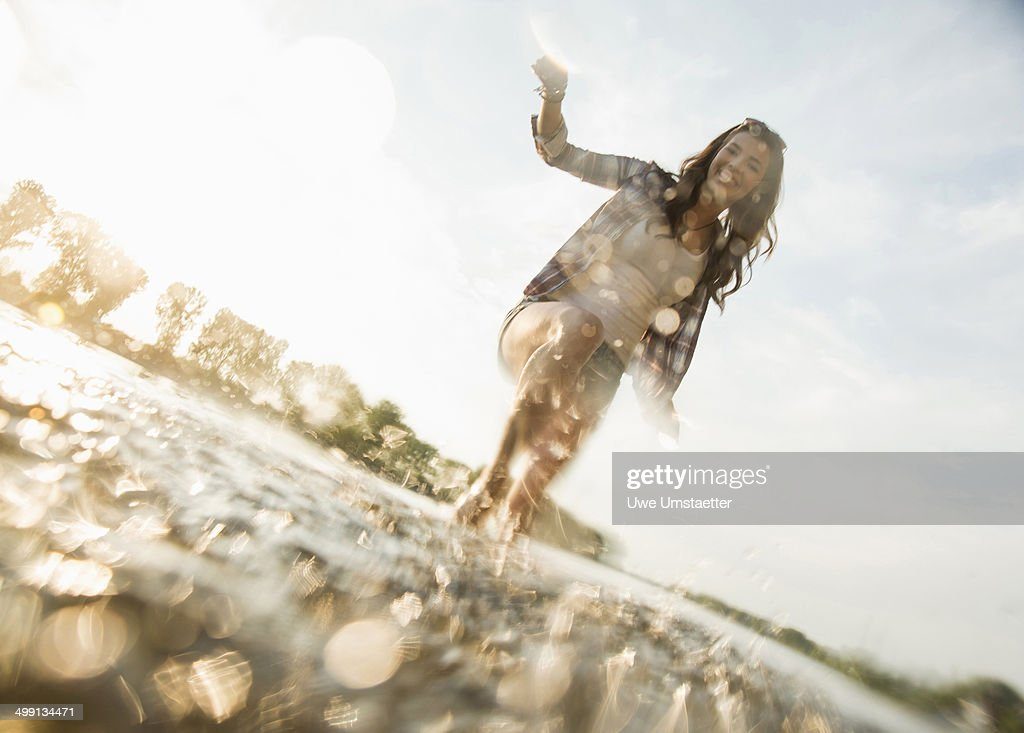Young woman paddling in lake