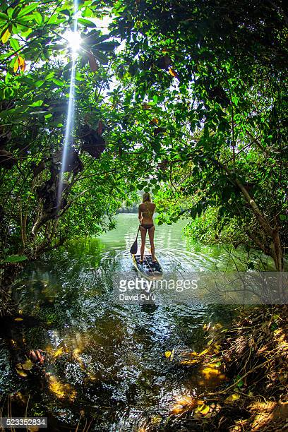 Young woman paddling out onto Balian River, Bali, Indonesia