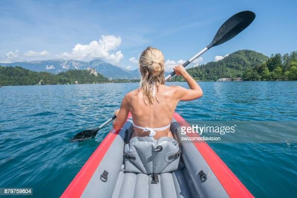 Young woman paddling red canoe in Slovenia