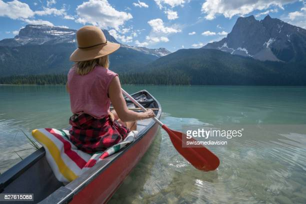 Young woman paddling red canoe on turquoise lake