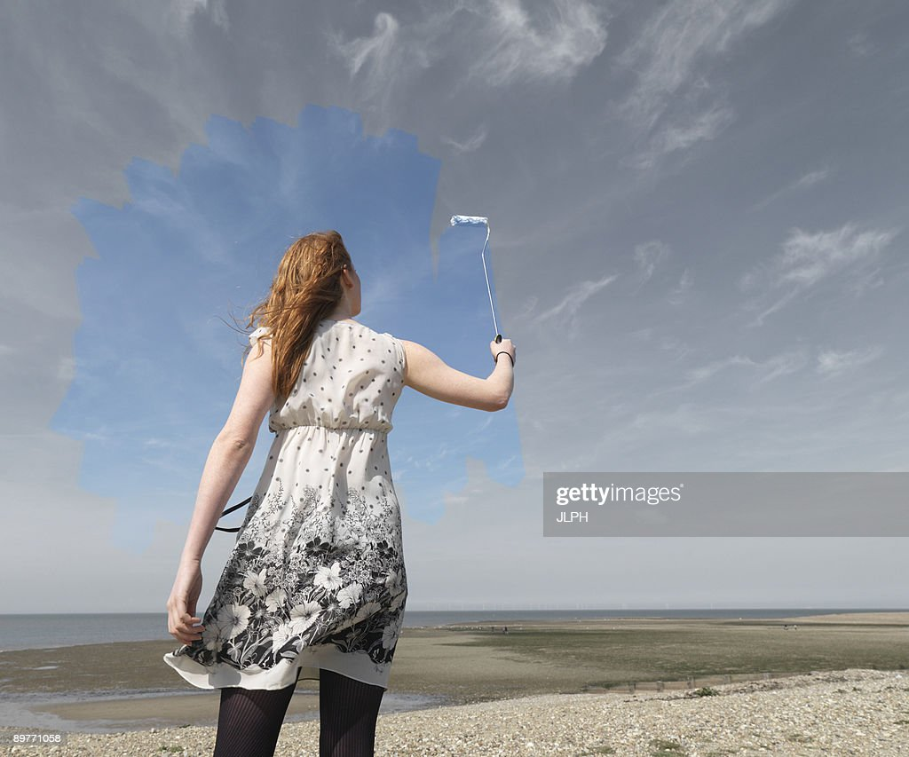 Young woman painting grey sky blue : Stock Photo