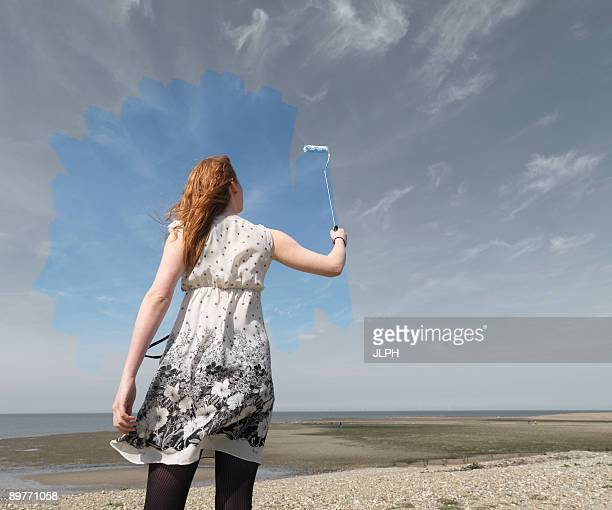 Young woman painting grey sky blue