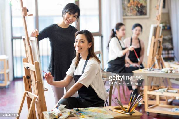 Young woman painting in art class