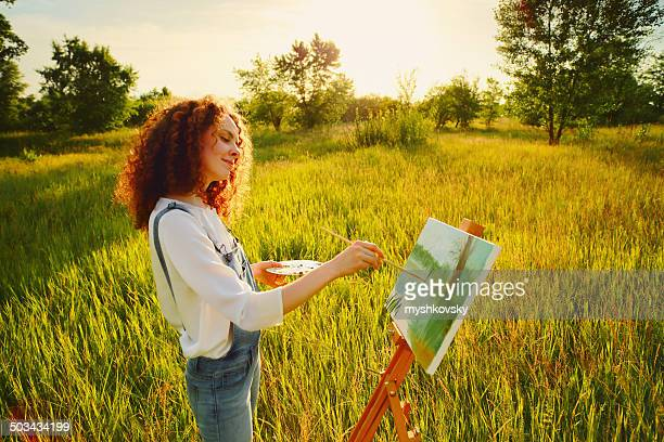 Young woman painting landscape in open air