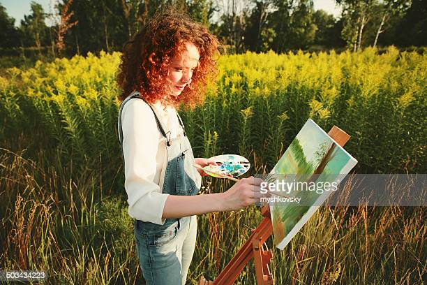 Young woman painting landscape in open air.