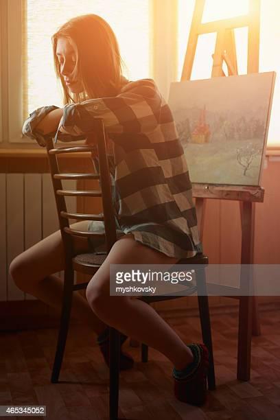 Junge Frau painting Landschaft in der Nähe der Fenster