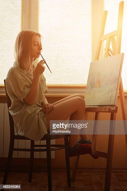 Jeune femme peinture paysage près de la fenêtre