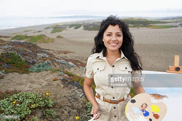 Young woman painting on beach (portrait)