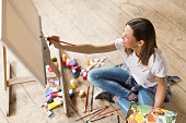 Young woman sitting on the floor and painting on canvas