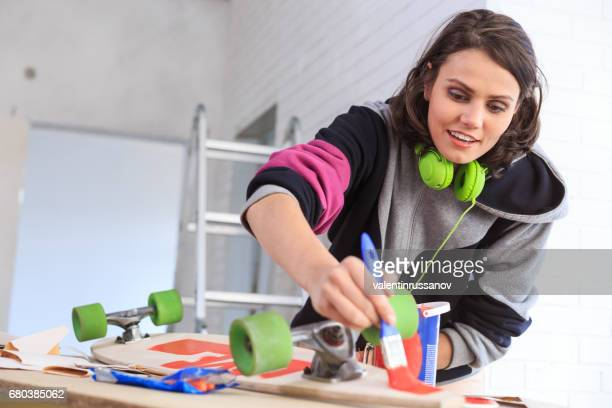 Young woman painting skateboard