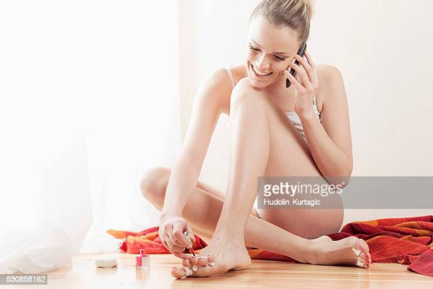 Young woman painting toenails