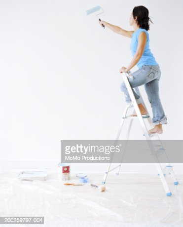 Young woman painting wall, using roller, side view