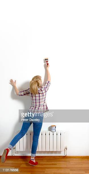 Young woman painting wall with copy space