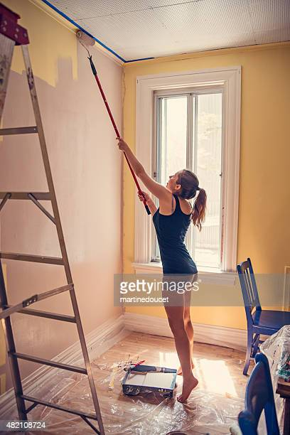 Young woman painting walls with an extended rollerbrush.