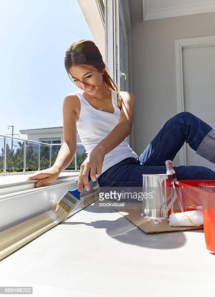 Jeune femme peinture bordure de fenêtre