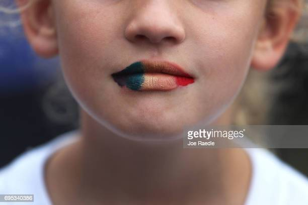 A young woman paints her lips in the gay pride colors as she attends a one year anniversary memorial service for victims of the mass shooting at the...