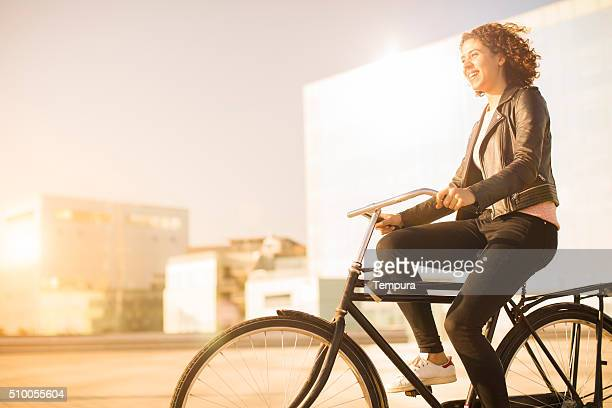 Young woman parking her bicycle in Barcelona.