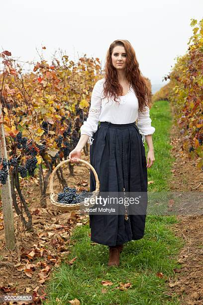 Young woman passes through in the middle of  vineyard