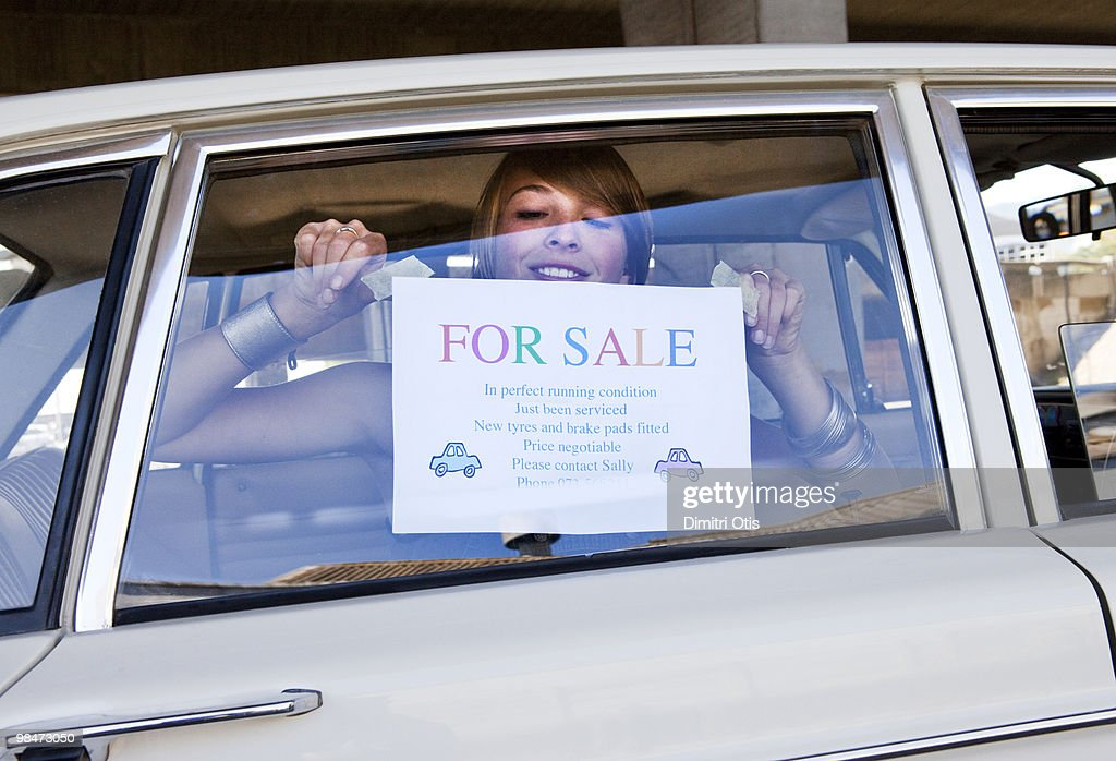 Young woman pasting 'For Sale' sign on her car