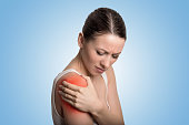 Injured joint. Young woman patient in pain having painful shoulder colored in red. Medicine and health care concept. Blue background