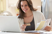 Young woman paying bills online