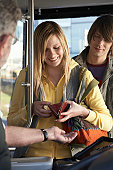 Young woman paying bus fare to driver, smiling