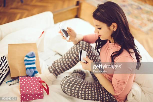 若い女性は彼女のお支払いのクレジットカードでの携帯電話